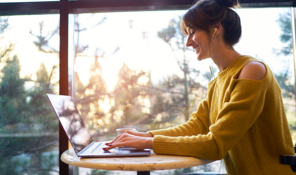 shows woman writing blog article on her laptop